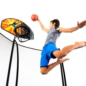A boy in grey tanktop and blue shorts playss with a trampoline basketball hoop set