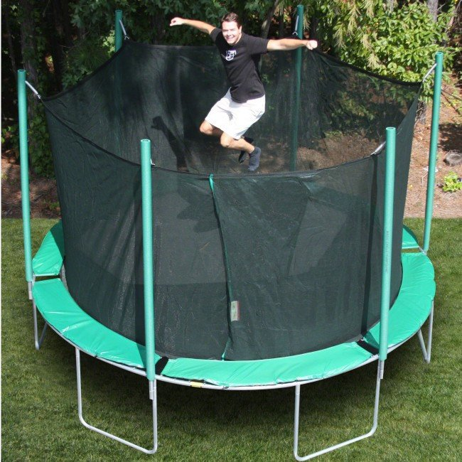 a smiling man in khakis bounces on green, round trampoline with enclosure