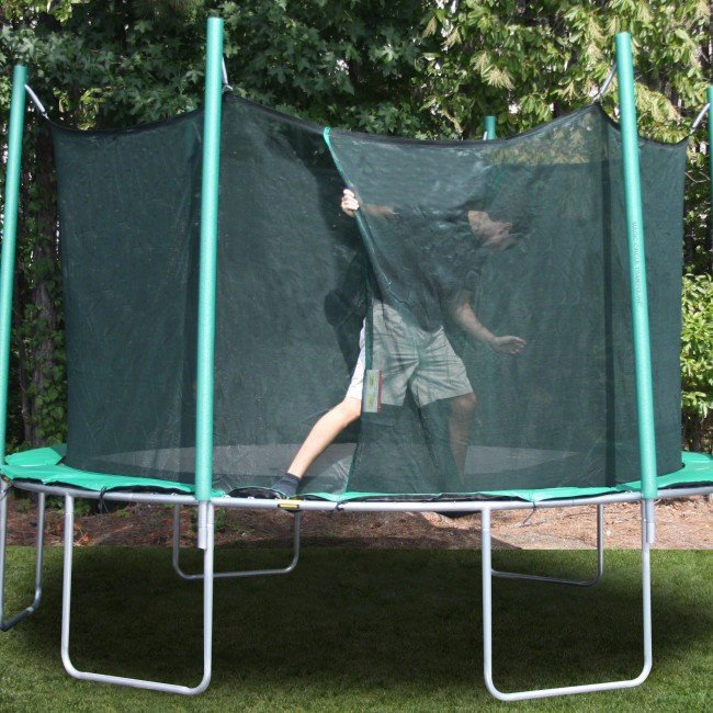 A man in khaki shorts, black shirt, and socks climbs out of a trampoline safety enclosure