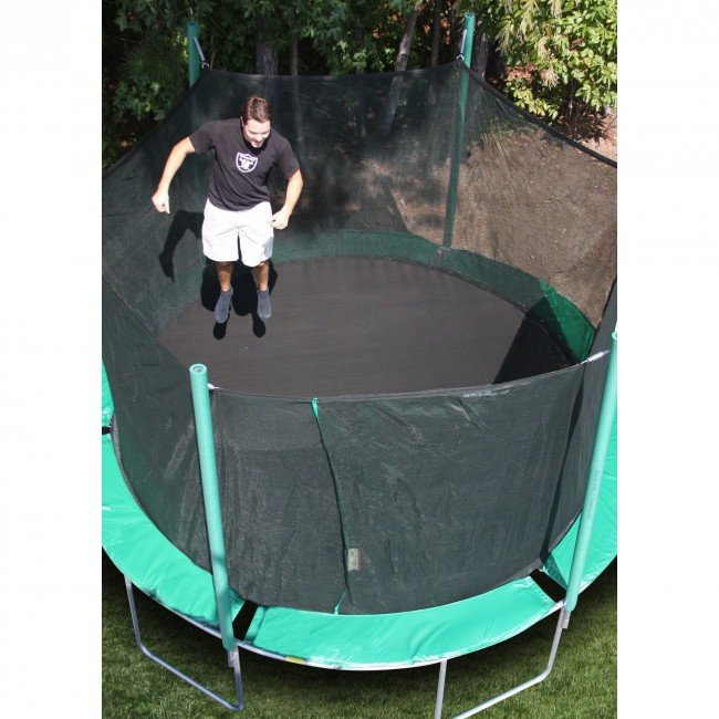 A man in his twenties jumps on a green trampoline.