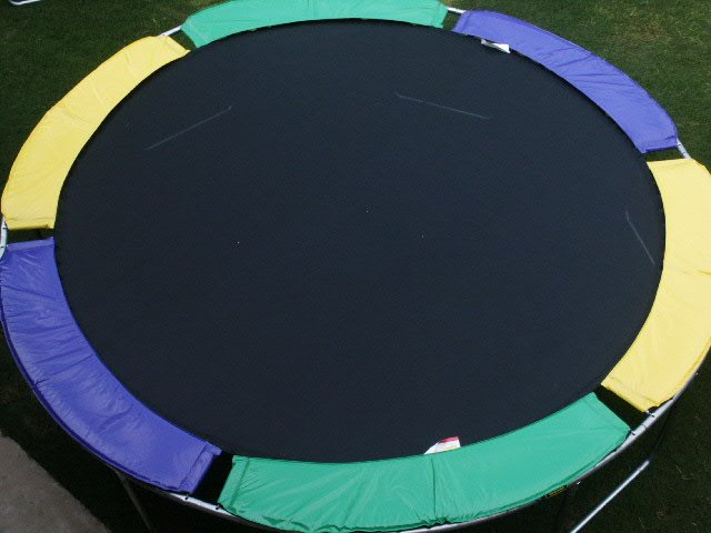 An overhead view of a purple, yellow, and green trampoline without net enclosure