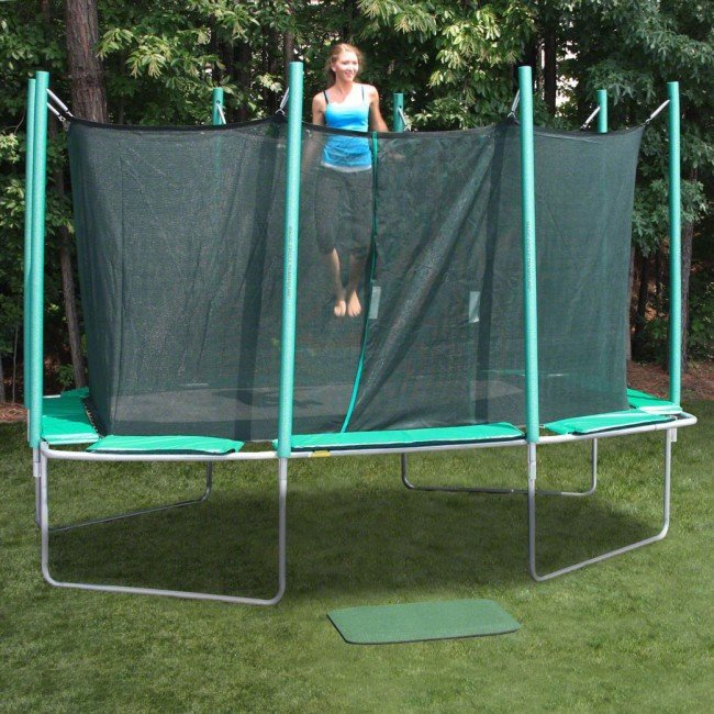 A cute teenage girl dressed in blue tank top and yoga pants jumps on a Magic Circle trampoline