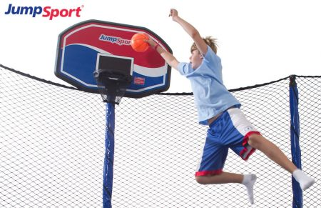 Young boy jumping and dunking his JumpSport ProFlex trampoline basketball hoop