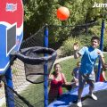 A group of kids watch breathlessly to see if their friends shot makes it into the trampoline hoop
