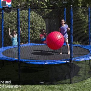 A young girl jumps on a trampoline with safety skirt while mother and brother watch from grass