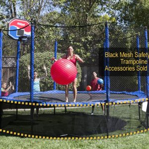 a woman in red bathing suit jumps on a trampoline with black mesh safety skirt while holding a big red ball