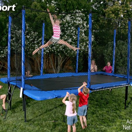 A little girl does gymnastics tricks on her rectangular trampoline
