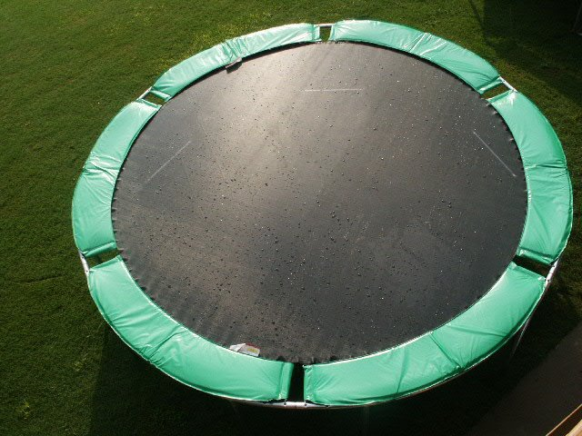 A green trampoline without safety net, in rain on lush green grass