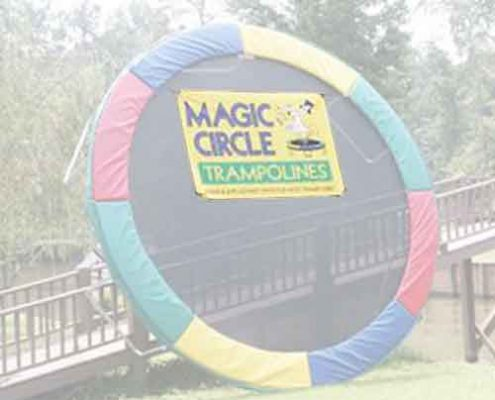 A Magic Circle trampoline leaned up against a fence
