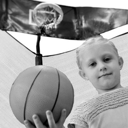 A little blond girl holds a basketball next to a trampoline basketball hoop