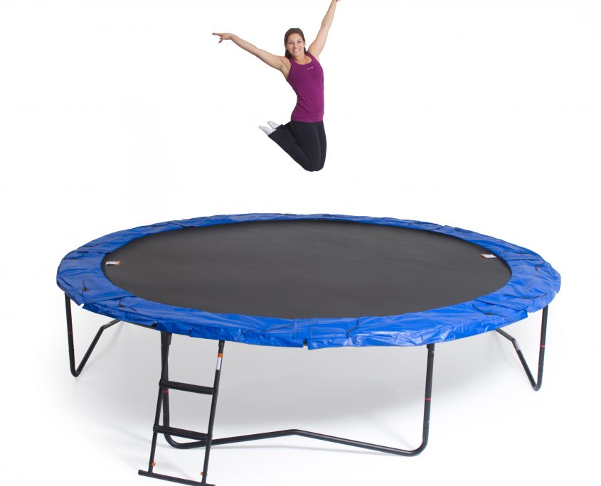 A woman bouncing and posing on a JumpSport trampoline without safety enclosure