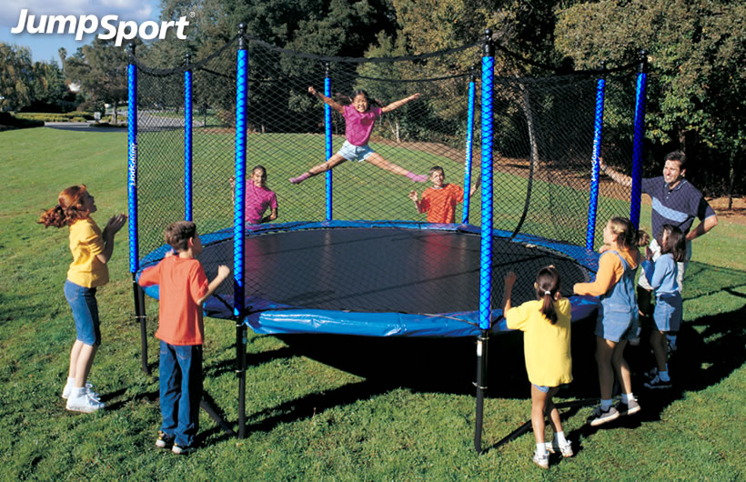 a little girl jumping on a JumpSport SoftBounce trampoline while a group of kids watch and cheer