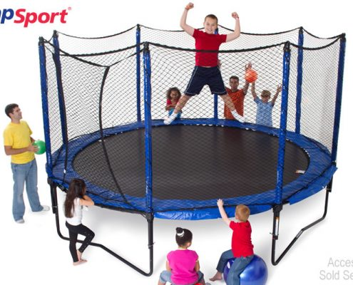 a kid flexing his muscles, while a group of kids watch him jump on a JumpSport trampoline