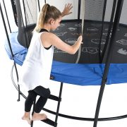 A girl in white tank top and black yoga pants climbs a ladder into a trampoline