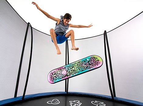A boy jumps above a colorful trampoline skate deck