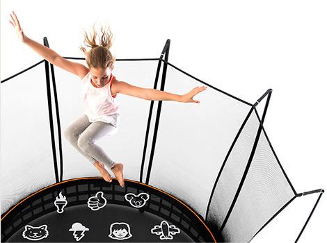 Girl in grey pants and white shirt flails her arms as she jumps on a tramp