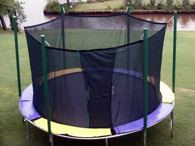 A round trampoline with net on a golf course next to a river