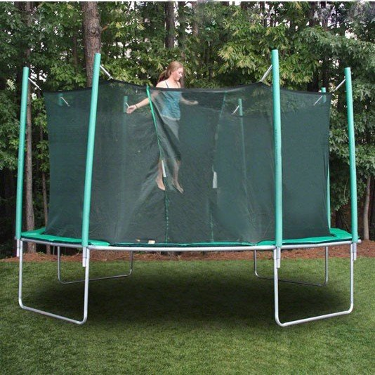 A teenage girl jumps on a green trampoline with net.