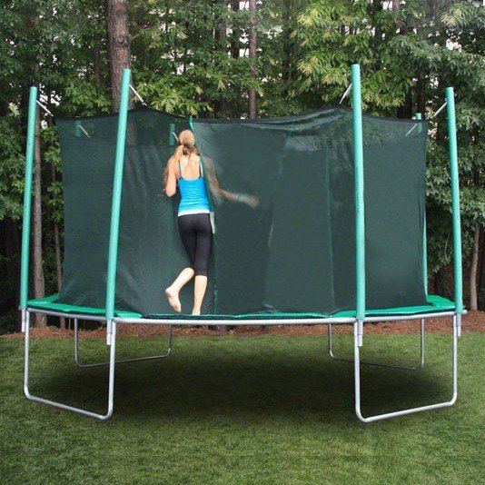 An attractive teenage girl with blue tank top, black yoga pants, and ponytail enters a trampoline safety enclosure.