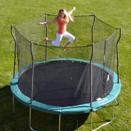 Blond mom jumping on turqouise trampoline in backyard