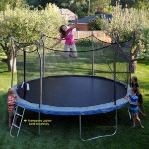 Brunette mom, with kids watching, jumps on a blue Propel Trampoline in backyard