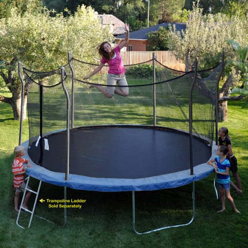 Brunette mom, with kids watching, jumps on a blue Propel Trampoline in backyard