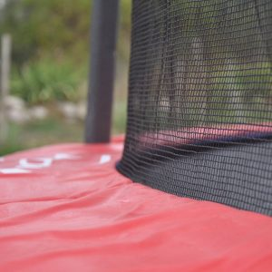 Close up picture of a red trampoline pad and safety net