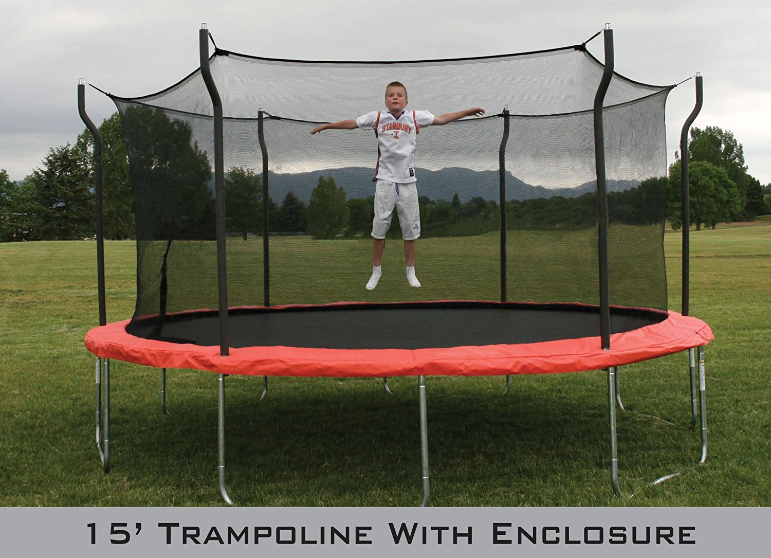 Young boy jumps on 15 foot trampoline with enclosure in grassy field