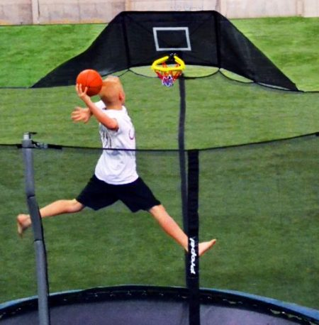 A 10-year old boy jumps to slam dunk his trampoline basketball hoop in his backyard
