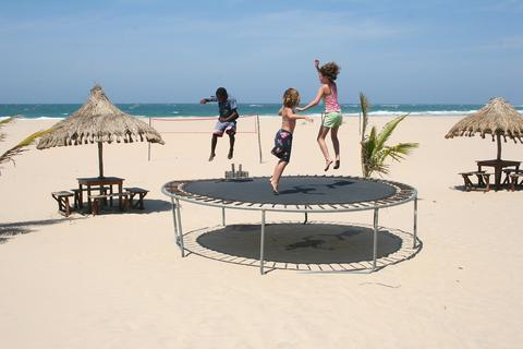 Two small children jump on trampoline at the beach