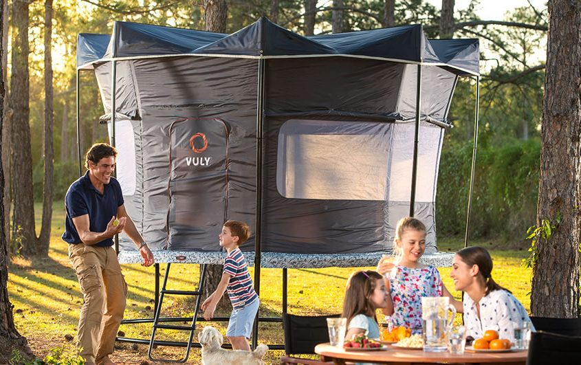 A dad plays with dog and son while mom and daughters eat all while camping