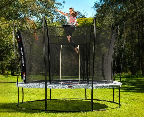 A teenage girl jump punches on a 14 foot Vuly 2 trampoline