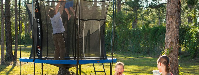 A dad stands on a trampoline holding his son in the air